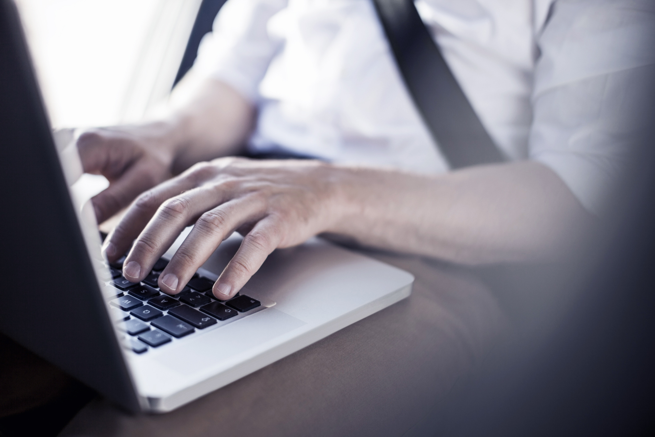 Midsection of businessman using laptop in taxi
