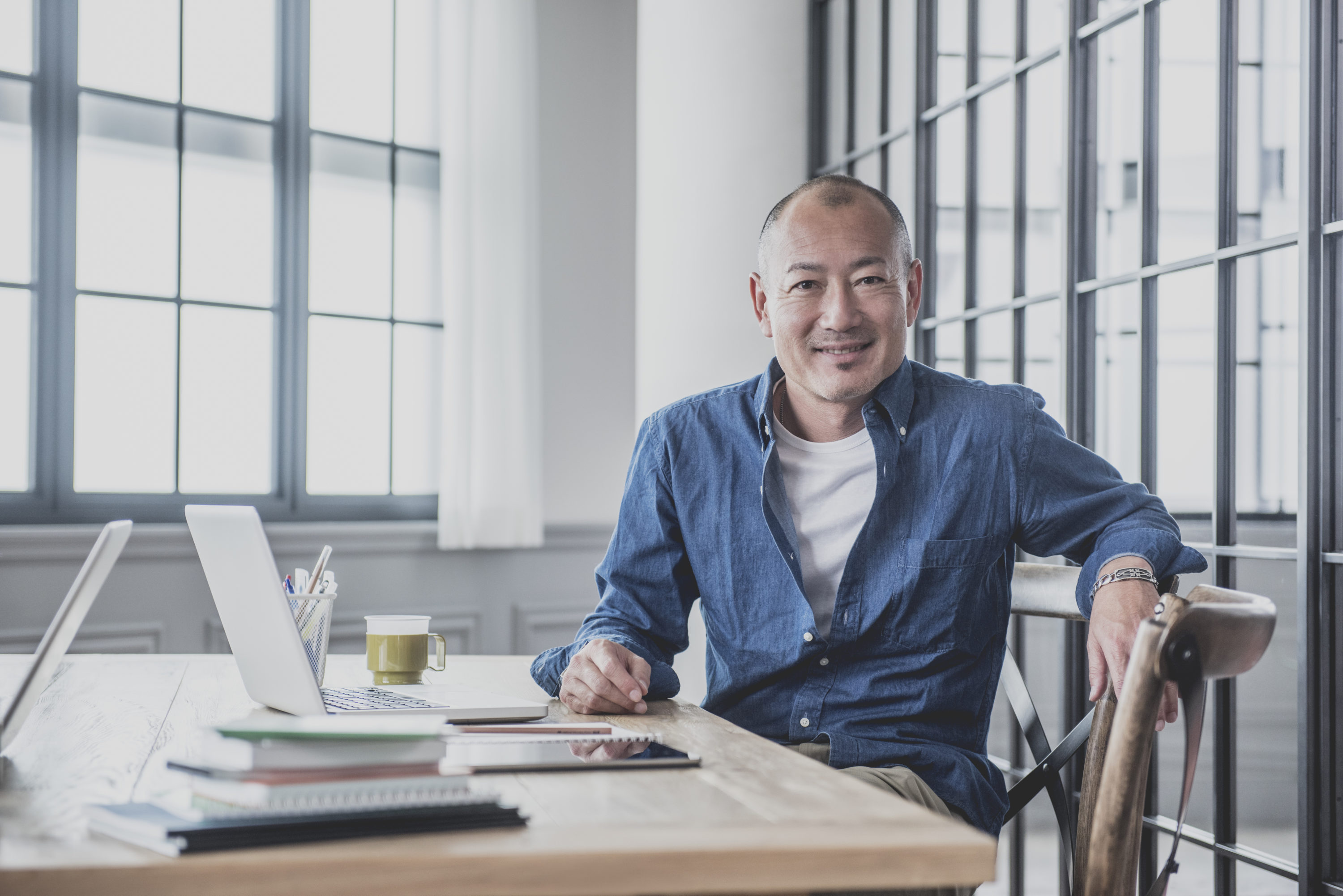Japanese professional male worker sitting in modern studio with laptop, smiling to camera, Tokyo, Japan. Candid portrait of Asian man at work in creative agency.