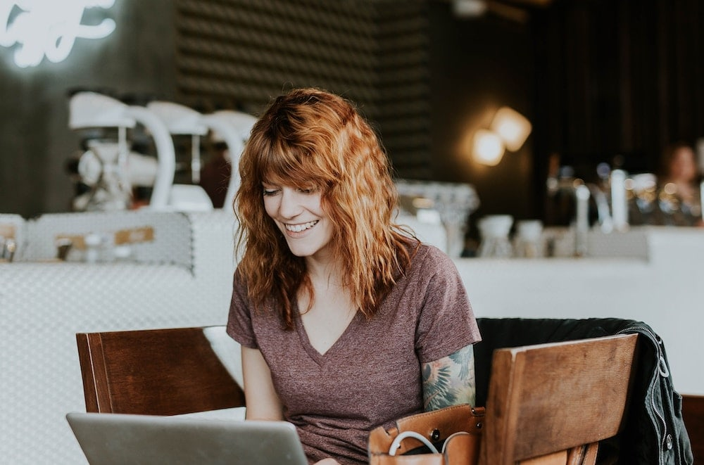 Woman using a laptop at a coffee shop and having a great time